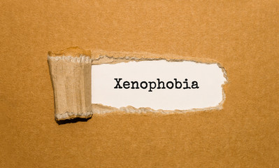The text Xenophobia appearing behind torn brown paper