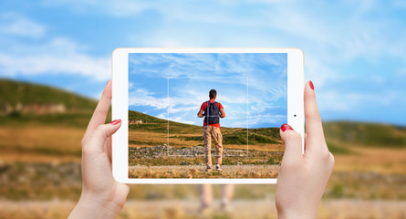 Female hands holding white tablet and taking photo of man with backpack on the top of the mountain