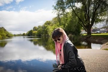 Beautiful woman sitting at riverbank