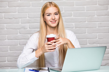 Attractive blond business woman working on her laptop and drinking coffee in her office