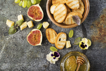 Ingredients for appetizing sandwiches for breakfast or snacks from grilled bread, figs, cheese, grapes, honey and nuts on a gray stone background with edible flowers. Top view.