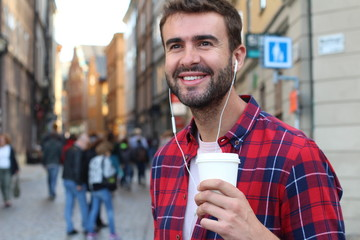 Gorgeous male holding a disposable cup of coffee in the a crowded city street