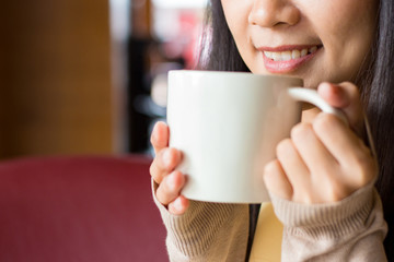 Asian woman holding white cup of coffee with both hand close to her mouth
