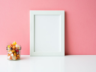 Blank white frame and lollipops in jar on a white table against the pink wall with copy space
