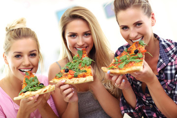 Fototapete - Three beautiful young women eating pizza at home