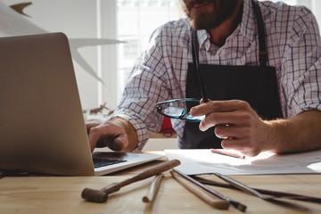 Craftsman using laptop at desk