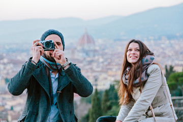 young man taking photograph  against view of Florence from above