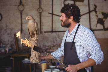 Thoughtful craftsman looking at bird sculpture