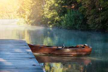 Rowing boat at wooden pier on lake