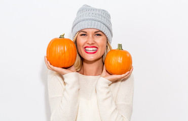 Young blonde woman holding pumpkins for halloween Wall mural
