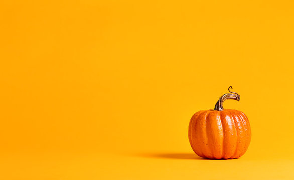 Halloween pumpkin decorations on a yellow-orange background