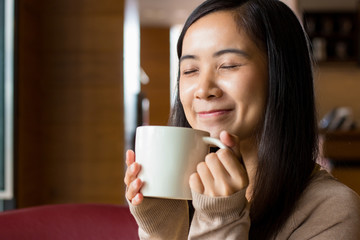 Asian woman drinking coffee from white coffee cup with blurry background of coffee shop