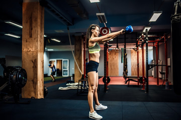 Attractive female athlete performing a kettle-bell swingin crossfit gym.