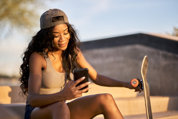 young happy african american woman with skateboard in skatepark using smart phone