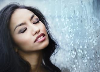 Beautiful womans face water falling down beside her skin