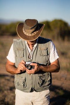 Man adjusting the lens of camera  during safari vacation