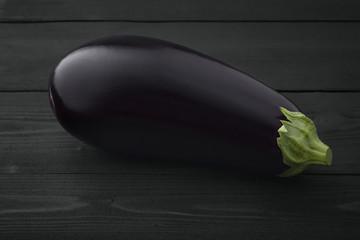 One fresh beautiful eggplant on dark wooden background.