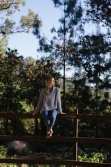 Full length of thoughtful female hiker sitting on wooden fence