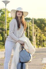 Young beautiful girl with hat on her head with suitcase at train station