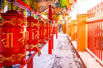 Red cylinders with Buddhist mantras and color flags. Buddhist Temple Datsan Gunzechoinei in Sankt-Peterburg. Russia.