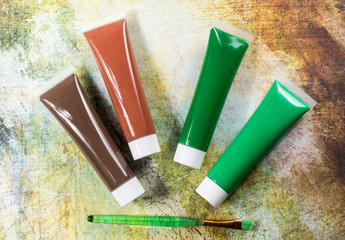 Colours of the nature - mix of green and brown - home or office interieur design concept, tubes with acrylic paint and green brush