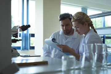 University students discussing on notepad in laboratory