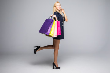 Time to buy new dresses. Beautiful young woman in pretty dress looking at camera and holding shopping bags standing against grey