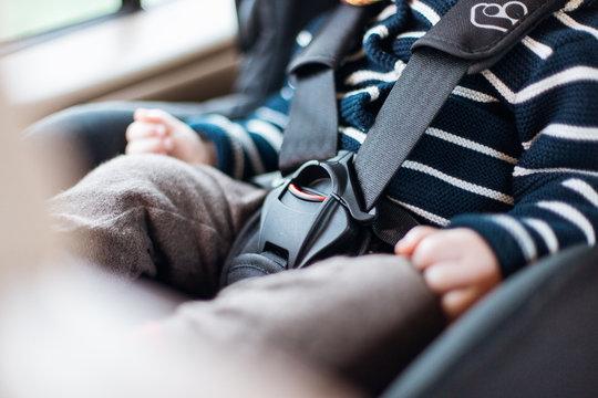 Kind in einem Autositz mit Gurt