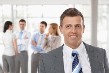 Middle-aged businessman in front of colleagues