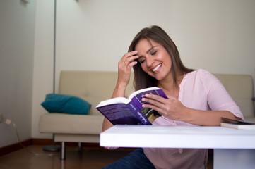 Mujer leyendo libro en la sala de su casa
