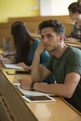 Thoughtful male student with classmates at desk