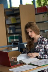 Young female student using laptop while studying