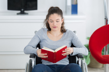 young disabled woman on wheelchair reads book