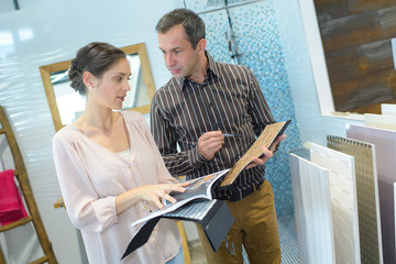 adult happy couple looking at bathroom tile in furniture store