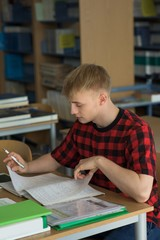 High angle view of young male student studying at desk
