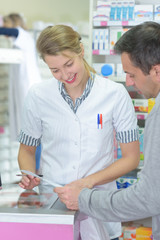 happy pharmacist showing drug to man customer at drugstore