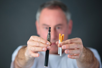 man comparing classic tobacco cigarette and electronic cigarette or vaporizer