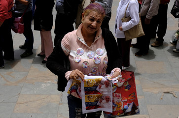 Hernandez, from Venezuela poses as she sells pins and flgas with the image of Pope Francis in front of Cathedral in Candelaria neighbourhood at Bolivar square in Bogota