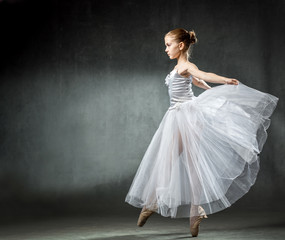 Ballet. Image of a flexible cute ballerina dancing in the studio. Beautiful young dancer. A ballerina is posing.