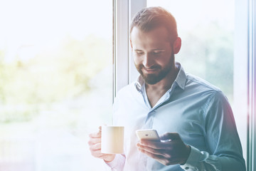 businessman holding morning coffee and reading phone