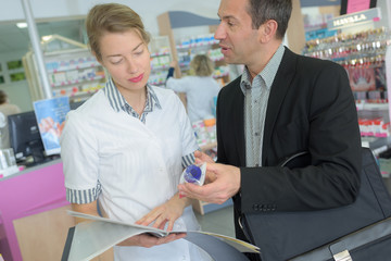 female pharmacist counseling customer about drugs