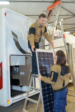 two electrical workers checking rv solar cell panel