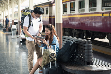 Couple traveler look at tablet happy at vintage trainstation