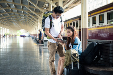 Couple traveler checking gps in tablet at trainstation