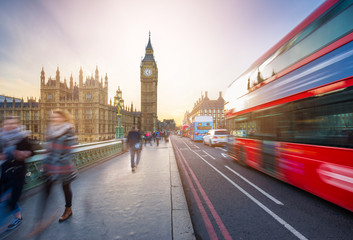 Foto op Aluminium Londen rode bus London, England - The iconic Big Ben and the Houses of Parliament with famous red double-decker bus and tourists on the move on Westminster bridge at sunset