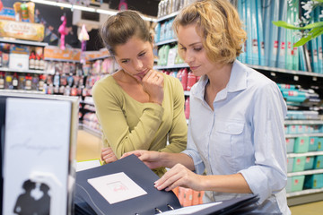 portrait of 2 female friends buying product in hardware store
