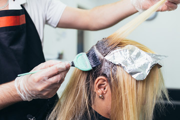 Hairdresser is dying female hair, making hair highlights to his client with a foil.