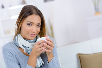 indoor portrait of a smiling caucasian woman drinking tea