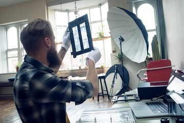 Side view of photographer looking at negatives in frame