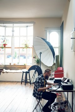Side view of photographer using graphics tablet while editing at